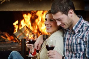 couple drinking wine next to a fireplace